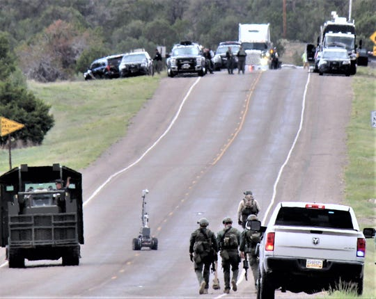 The camera robot moves down the highway with the battering ram to the left and tactical team vehicles at the top of the hill.