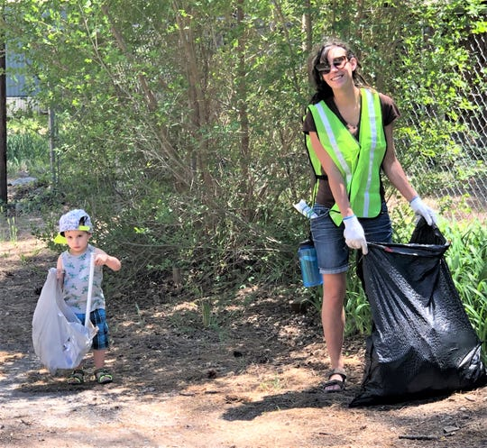 Some volunteers begin their cleanup careers at a young age as this toddler joins his mother.