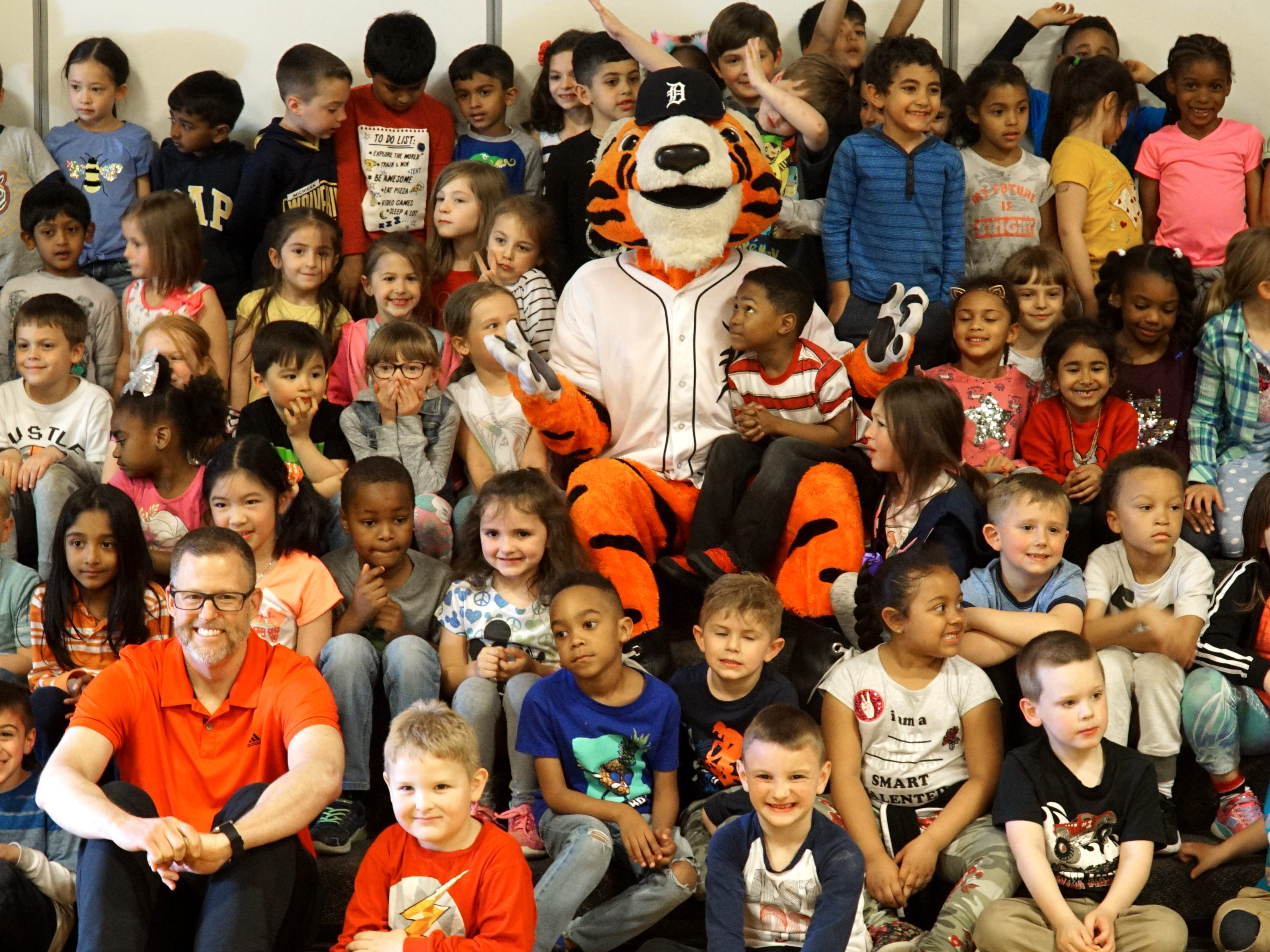 Eriksson principal Kevin Learned, lower left, poses with Paws and students after learning they made it possible for him to throw out a first pitch at a June 26th Tigers' game.