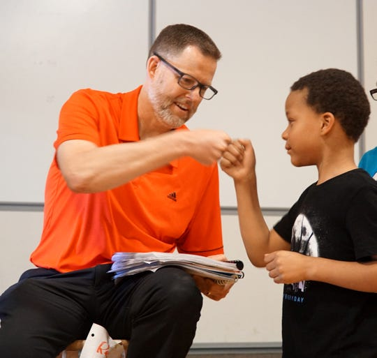 Eriksson principal Kevin Learned shares a fist-bump with first grader Saveion Griffin as he receives stacks of letters the school's kids wrote to the Detroit Tigers - asking that Learned be allowed to throw out a first pitch. At the time he was receiving the letter from the students Learned still did not know what they were up to.