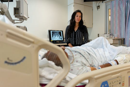 Lenh Vuong, a clinical social worker at Los Angeles County+USC Medical Center, checks on a former John Doe patient who was recently identified. (Heidi de Marco/KHN)