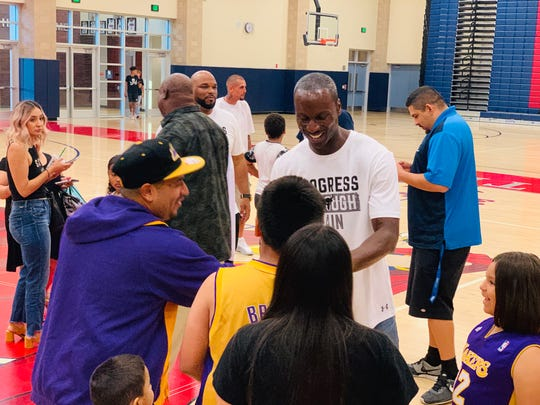 Andre Ingram speaks with a family of Laker fans Monday in Indio. Ingram made his debut for the Los Angeles Lakers 13 months ago, after spending 10 years in the G-League.