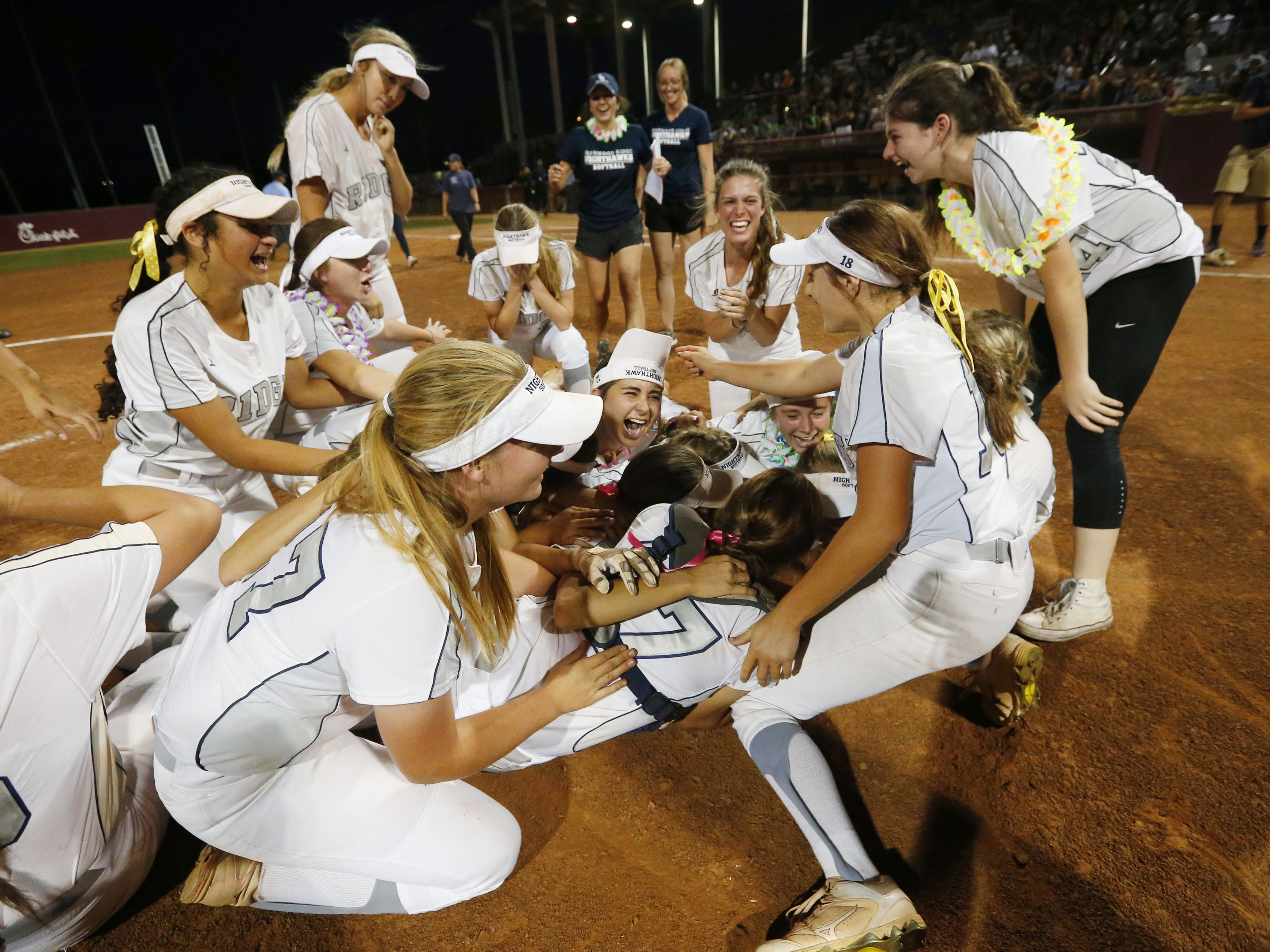 Ironwood Ridge players celebrate after beating Centennial 5-2 to win the 5A State Softball Championship in Tempe, Ariz. May 13, 2019.