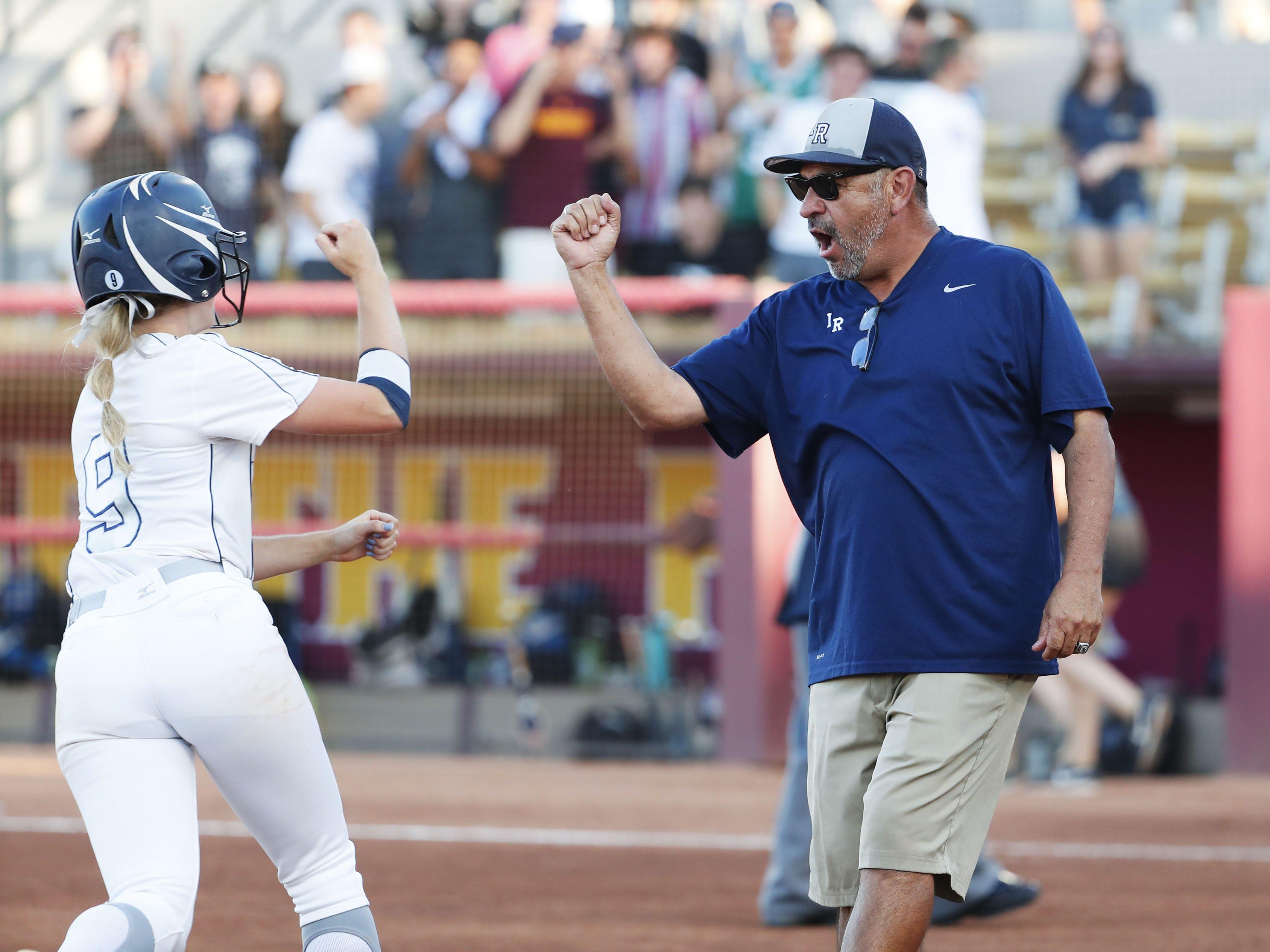 Ironwood Ridge head coach David Martinez congratulates Diana Nisbett (9) on her solo home run against Centennial during the 5A State Softball Championship in Tempe, Ariz. May 13, 2019.