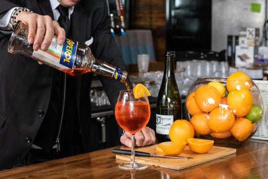 The Aperol Spritz at Pomo Pizzeria combines Aperol, orange juice, simple syrup and is topped with prosecco and a splash of soda water.