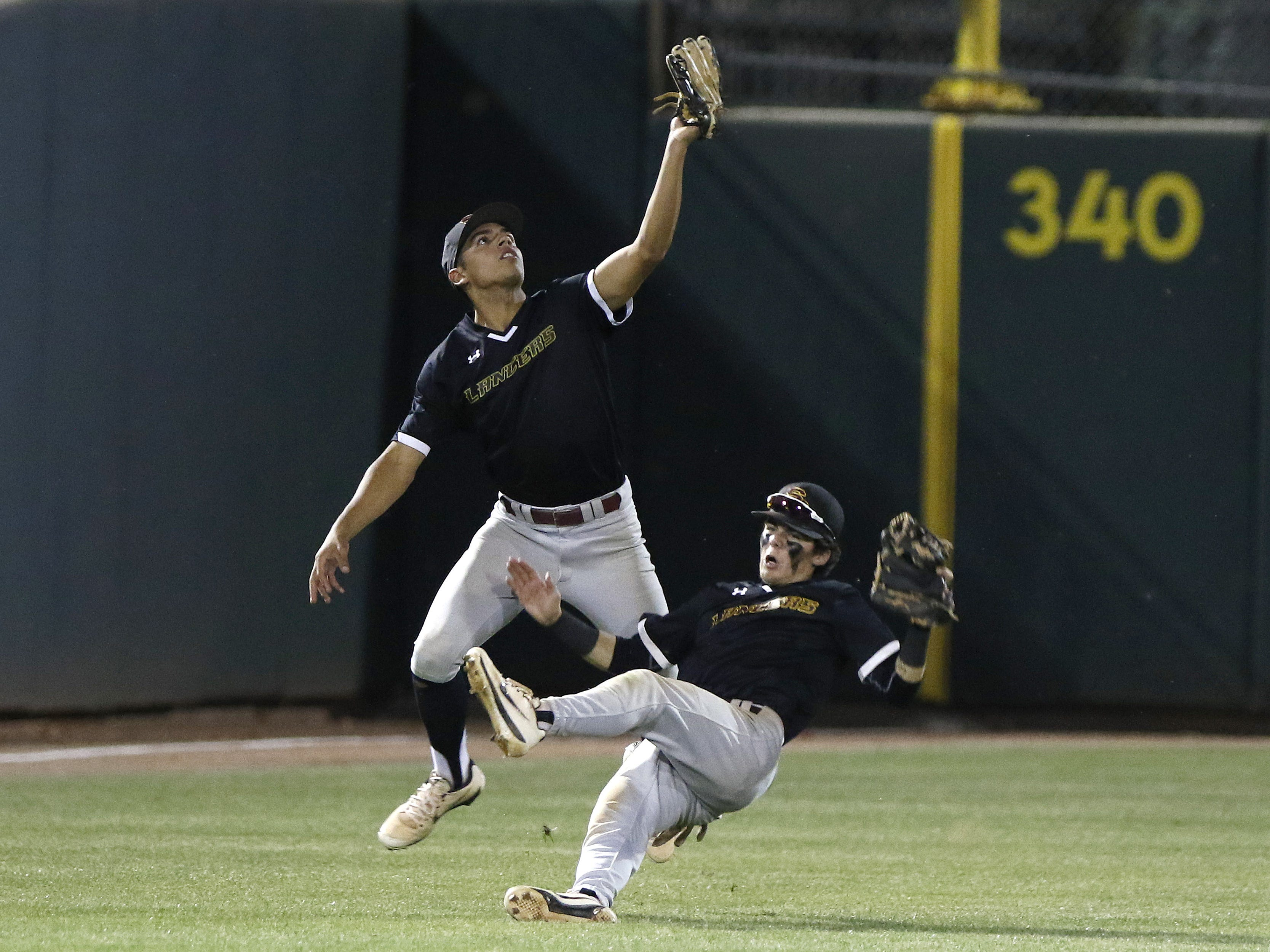 Salpointe's Ricky Santiago (left) and shortstop Romeo Ballesteros (falling) run into each other going after a fly ball against Mesquite during the 4A State Championship game in Mesa, Monday, May 13, 2019.