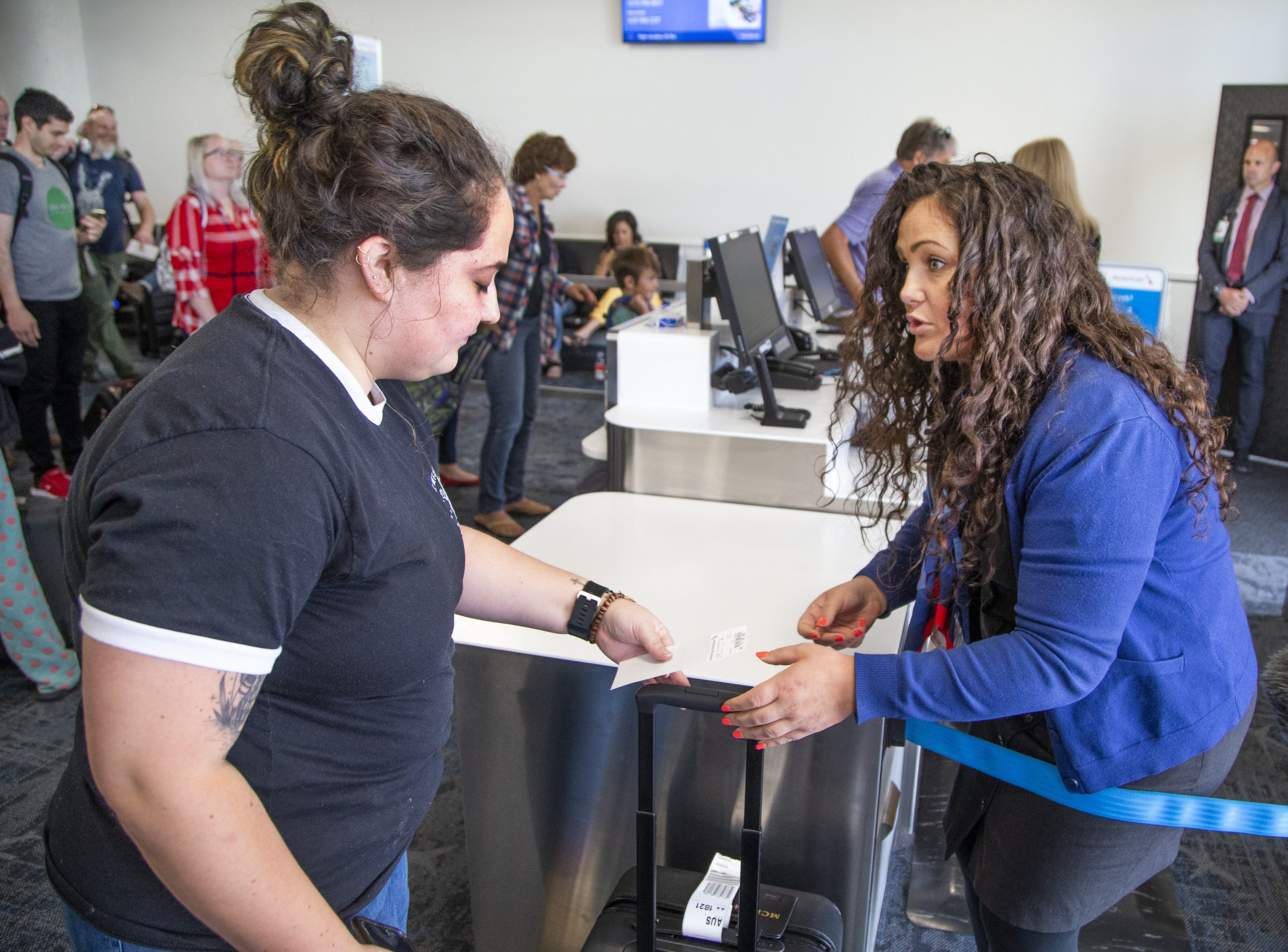 Meghan Rauker, 26, Austin, left, gate checks her bag with American Airlines gate agent Ashleigh Tenifa, before boarding an Airbus A-319 at Sky Harbor International Airport in Phoenix, Friday, May 10, 2019.  The flight was unloaded, serviced, cleaned, reloaded and reboarded for a flight to Austin within 30 minutes.