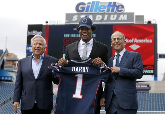 New England Patriots owner Robert Kraft (left) and his son, team president Jonathan Kraft, pose with first-round draft pick wide receiver N'Keal Harry (center) while introducing Harry at an NFL football news conference on May 9, 2019, at Gillette Stadium, in Foxborough.