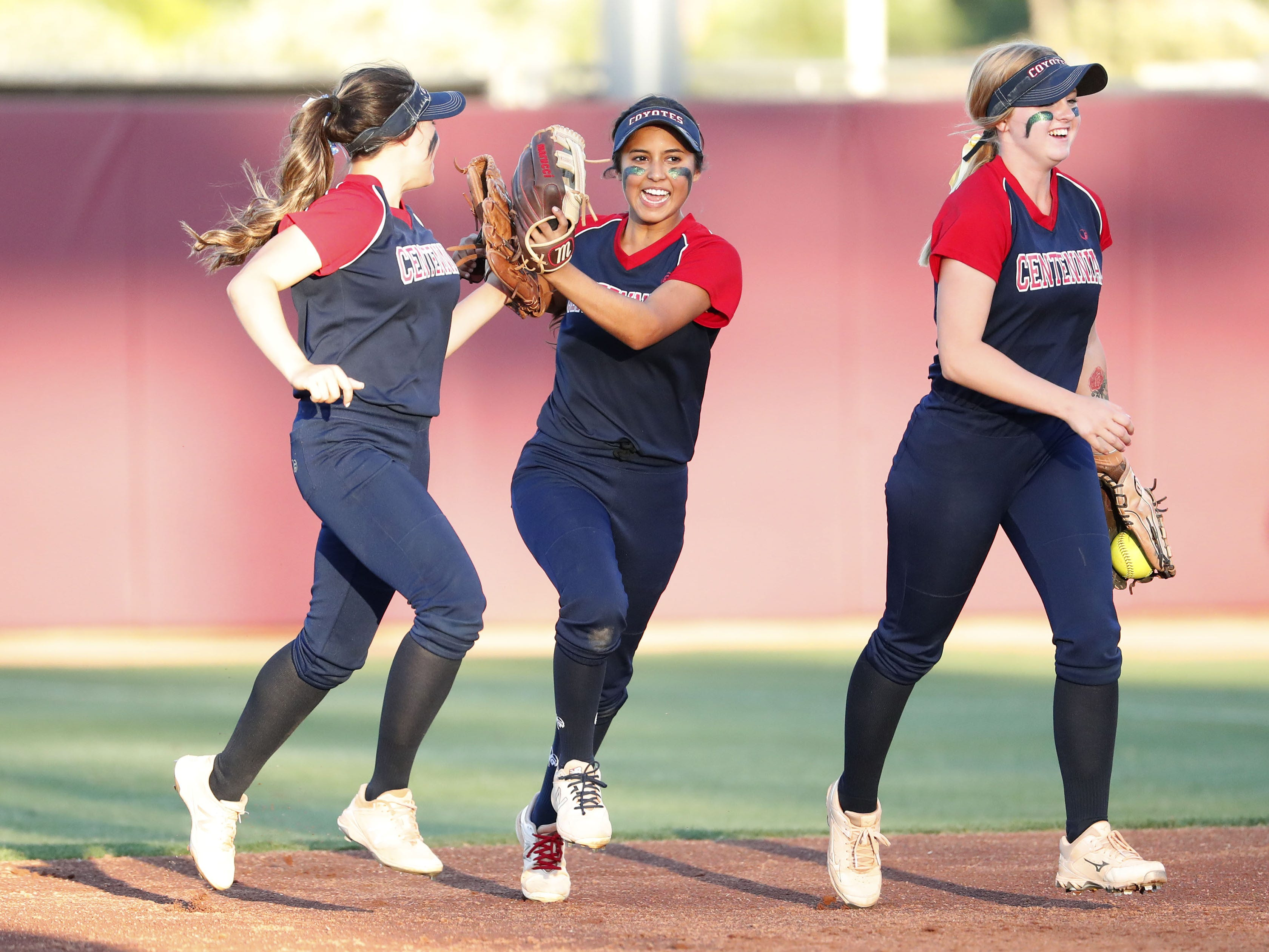 Centennial center fielder Jaydin Gonzalez (left) high-fives Natalie Vasquez between innings against Ironwood Ridge during the 5A State Softball Championship in Tempe, Ariz. May 13, 2019.