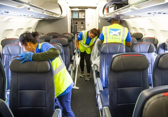 Workers clean an American Airlines Airbus A-319 at Sky Harbor International Airport in Phoenix after the plane arrived from Tucson, Friday, May 10, 2019.  The flight was unloaded, serviced, cleaned, reloaded and reboarded for a flight to Austin within 30 minutes.