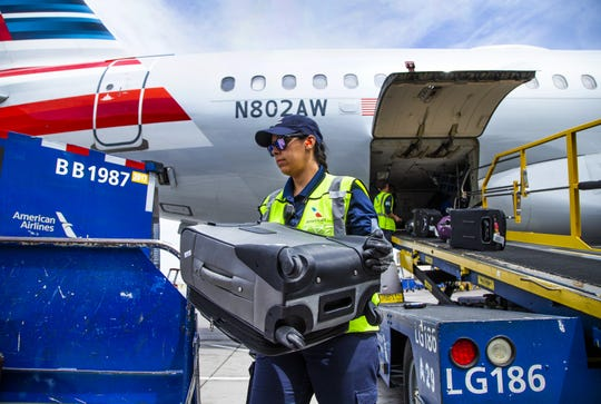 An American Airlines Airbus A-319 arrives at Sky Harbor International Airport after flying in from Tucson, Friday, May 10, 2019.  The flight was unloaded, serviced, cleaned, reloaded and reboarded for a flight to Austin within 30 minutes.  Fleet Service Agent Rita Peralta offloads baggage after the plane's arrival.