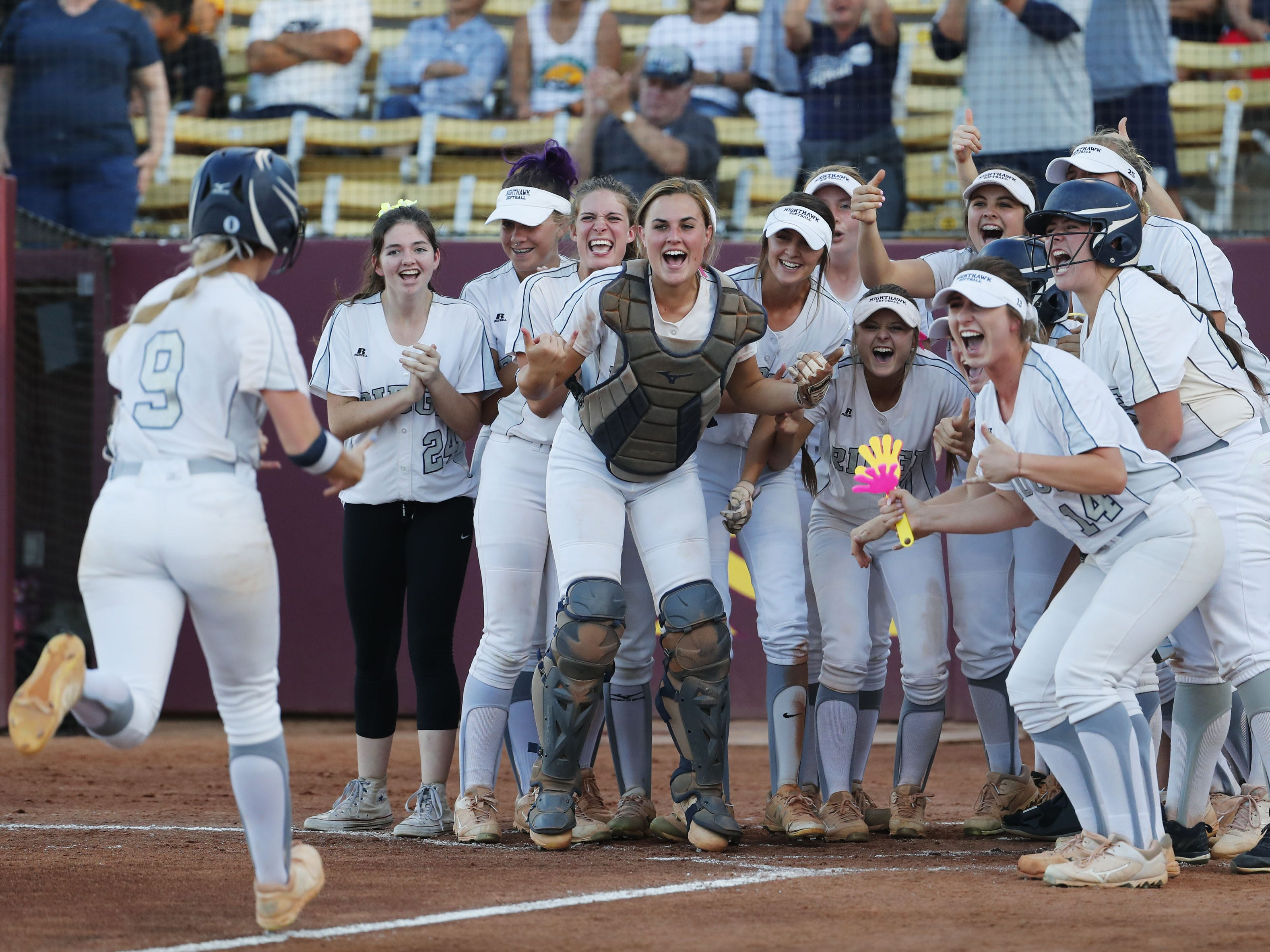 Ironwood Ridge shortstop Diana Nisbett (9) is greeted by her teammates after hitting a solo home run against Centennial during the 5A State Softball Championship in Tempe, Ariz. May 13, 2019.