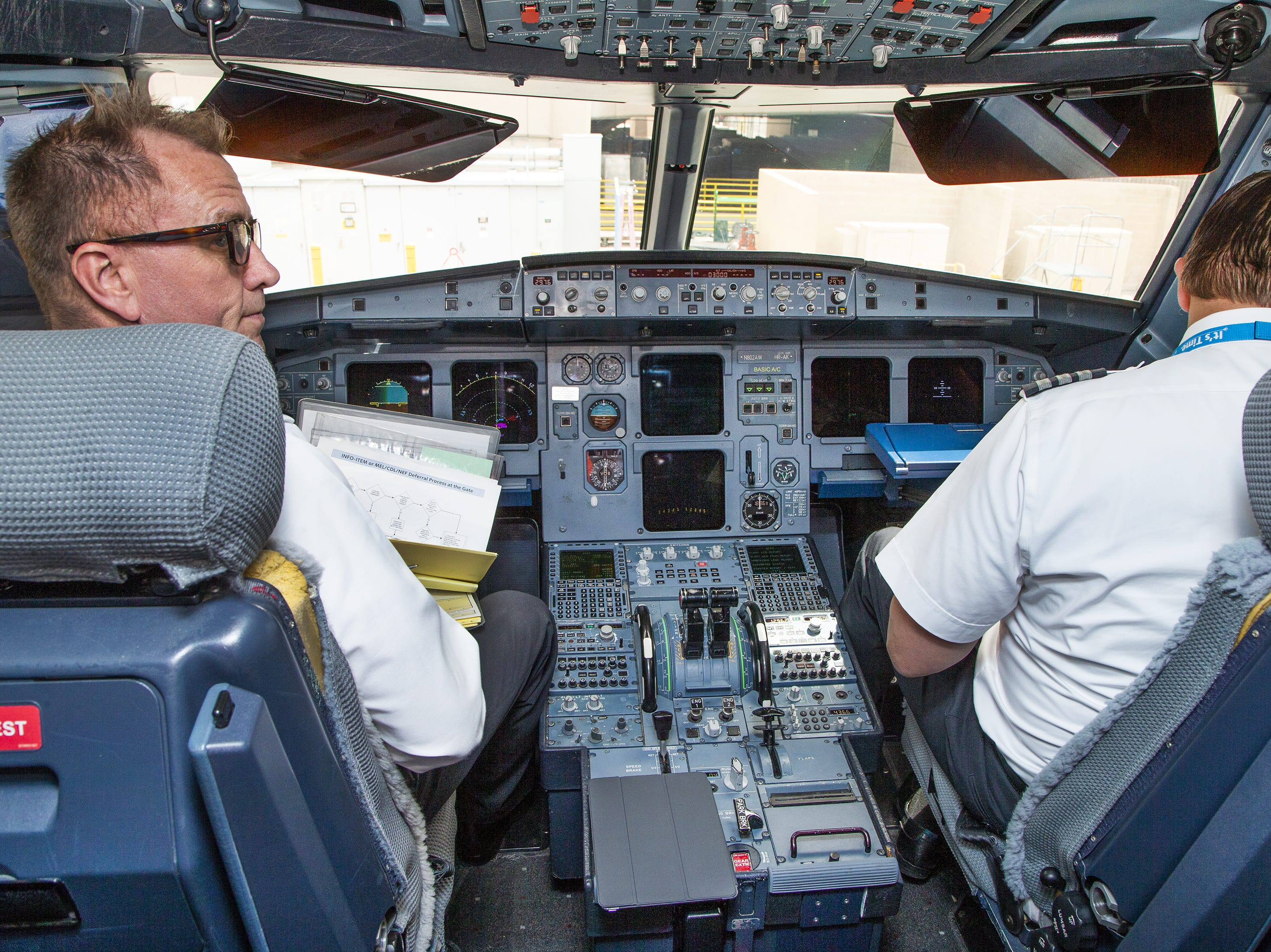 The pilot and co-pilot work in the cockpit after an American Airlines Airbus A-319 landed at Sky Harbor International Airport in Phoenix after a flight from Tucson, Friday, May 10, 2019.  The flight was unloaded, serviced, cleaned, reloaded and reboarded for a flight to Austin within 30 minutes.