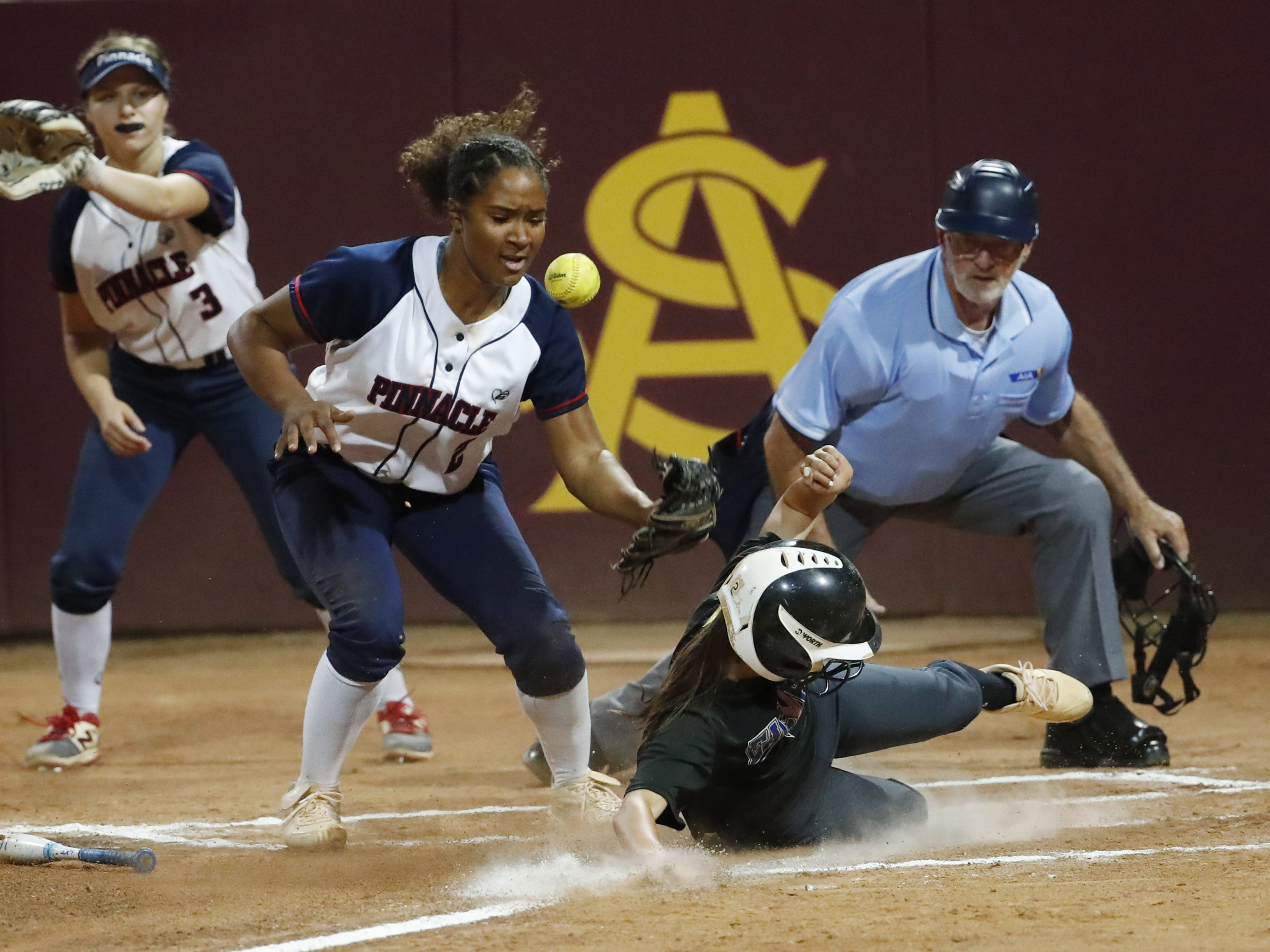 Sandra Day O'Connor's Ashley Herman (2) scores ahead of the tag by Pinnacle pitcher Morgan Smith (2) during the 6A State Softball Championship in Tempe, Ariz. May 13, 2019.
