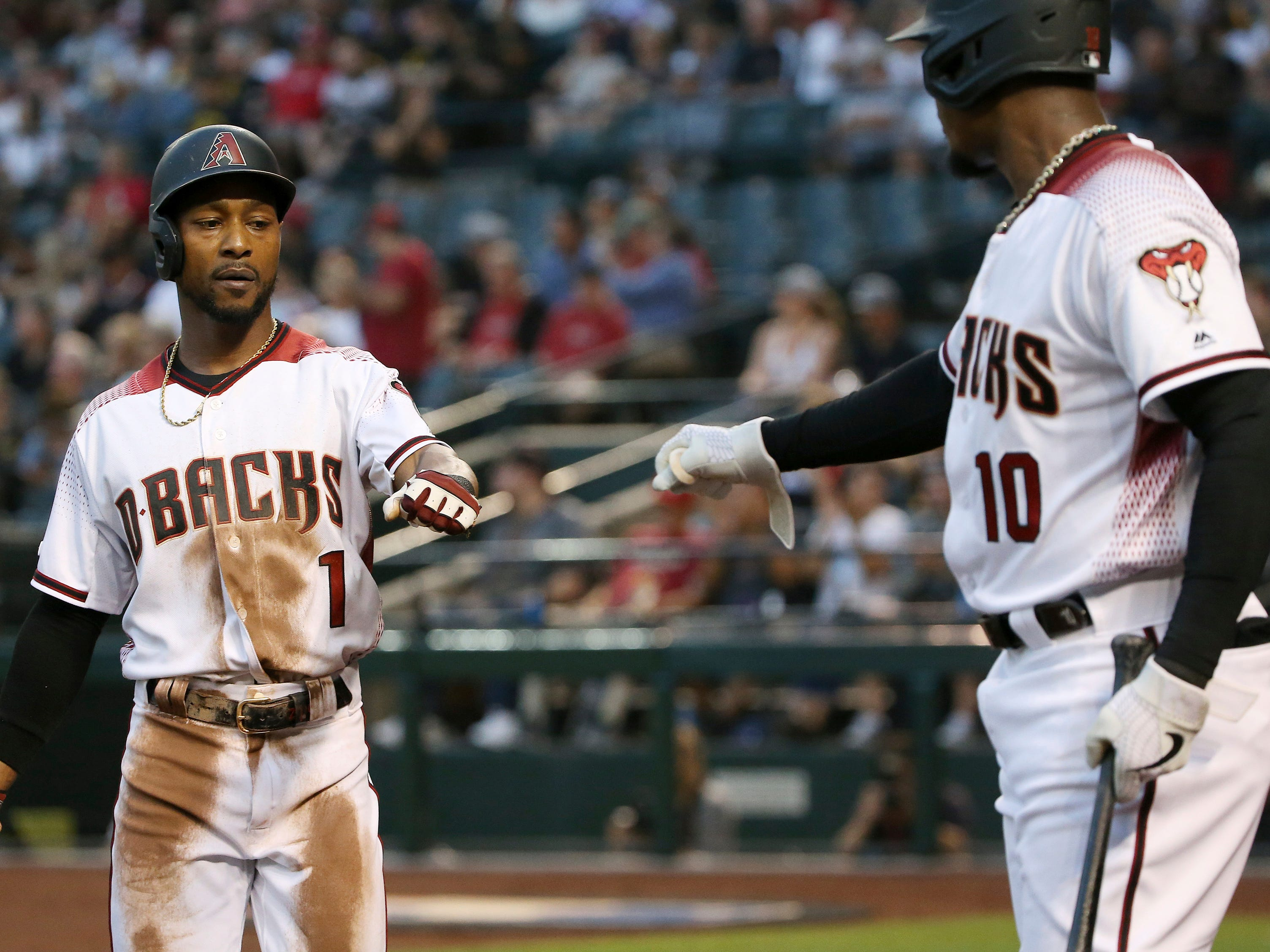 Arizona Diamondbacks' Jarrod Dyson (1) celebrates with teammate Adam Jones (10) after scoring a run against the Pittsburgh Pirates during the first inning of a baseball game Monday, May 13, 2019, in Phoenix.