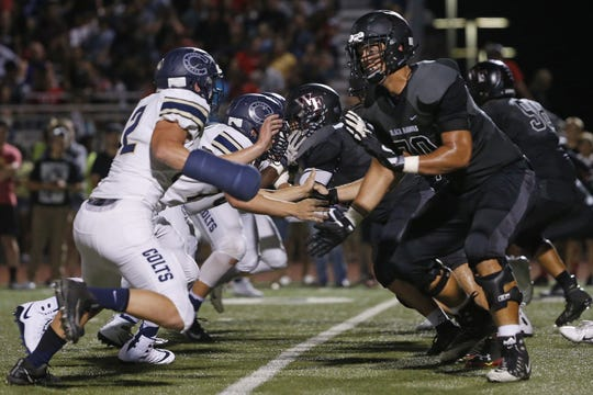 Williams Field's Noah Nelson (70) blocks Casteel's Cruz Webster (42) at Williams Field High School in Gilbert, Ariz. on Sept. 21, 2018.
