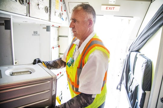 Workers restock the galley on an American Airlines Airbus A-319 at Sky Harbor International Airport in Phoenix after the plane arrived from Tucson, Friday, May 10, 2019.  The flight was unloaded, serviced, cleaned, reloaded and reboarded for a flight to Austin within 30 minutes.