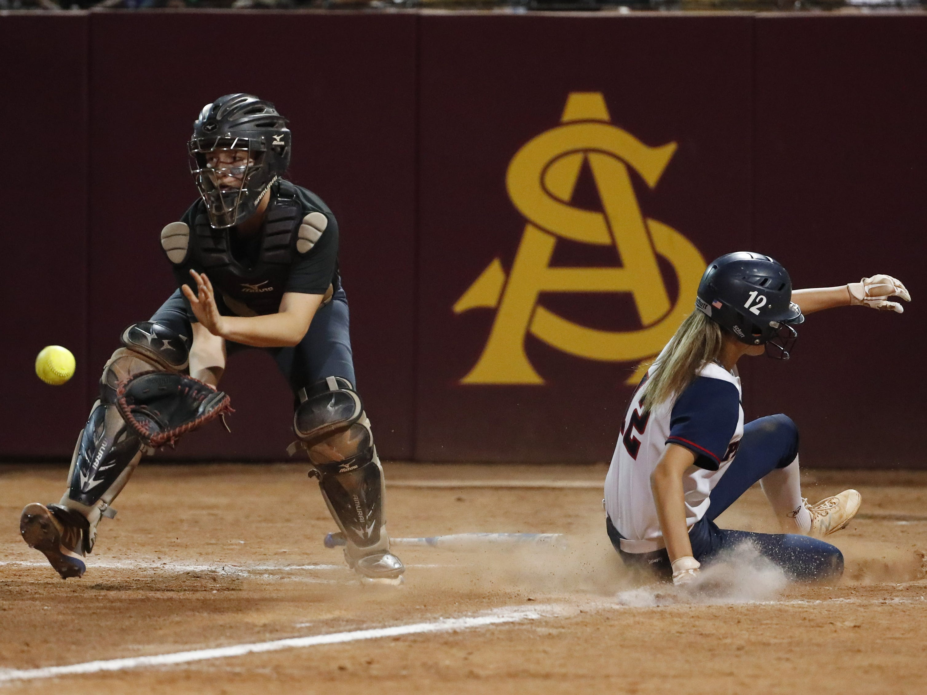 Pinnacle shortstop Emma Bullard (12) scores behind Sandra Day O'Connor catcher Jocelyn Erickson (8) during the 6A State Softball Championship in Tempe, Ariz. May 13, 2019.