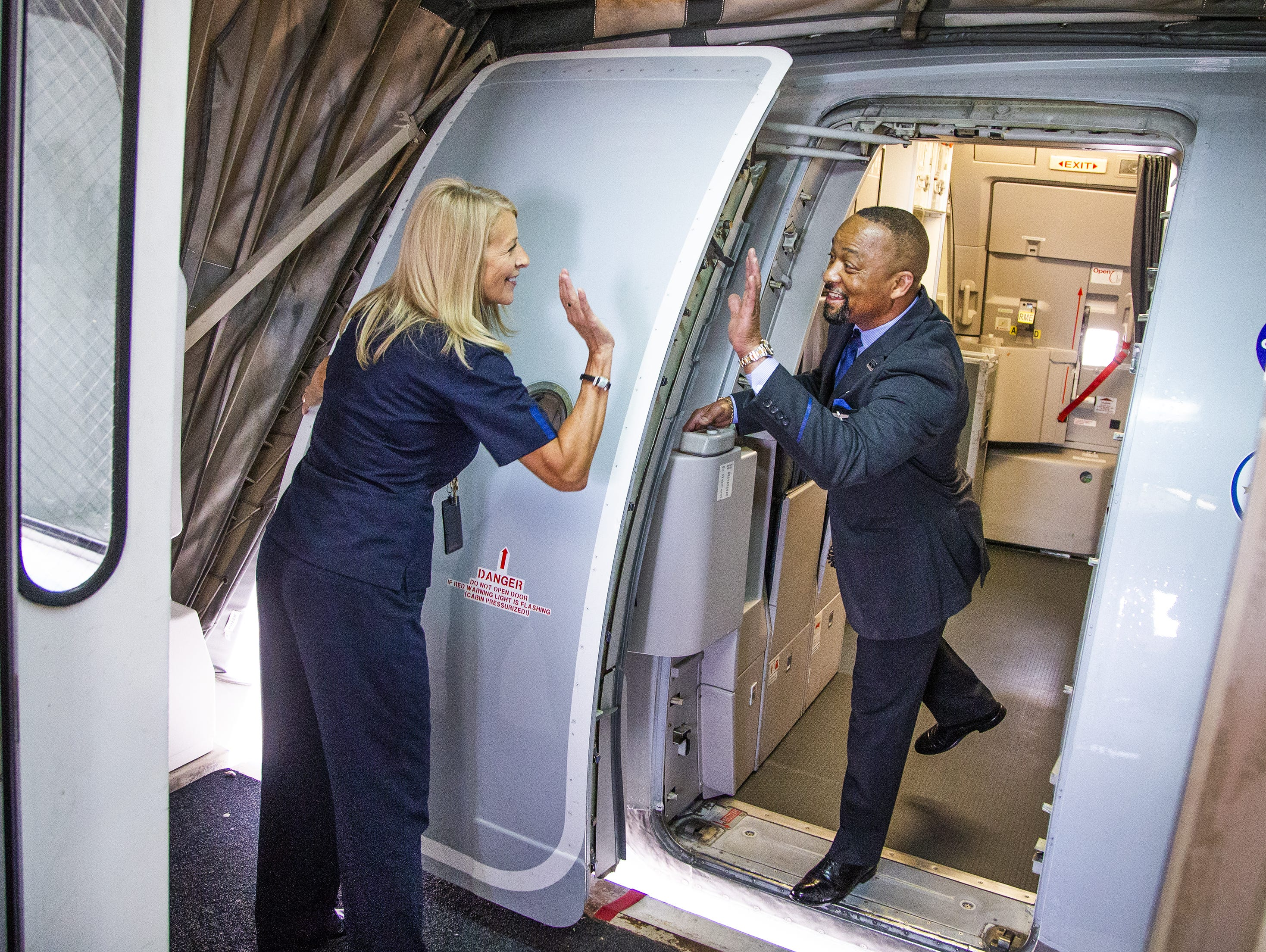 American Airlines gate agent Michel Wall, left, high-fives lead flight attendant Walter Davis, III, before Davis closes the door on an Airbus A-319 at Sky Harbor International Airport in Phoenix, Friday, May 10, 2019.  The flight was unloaded, serviced, cleaned, reloaded and reboarded for a flight to Austin within 30 minutes.