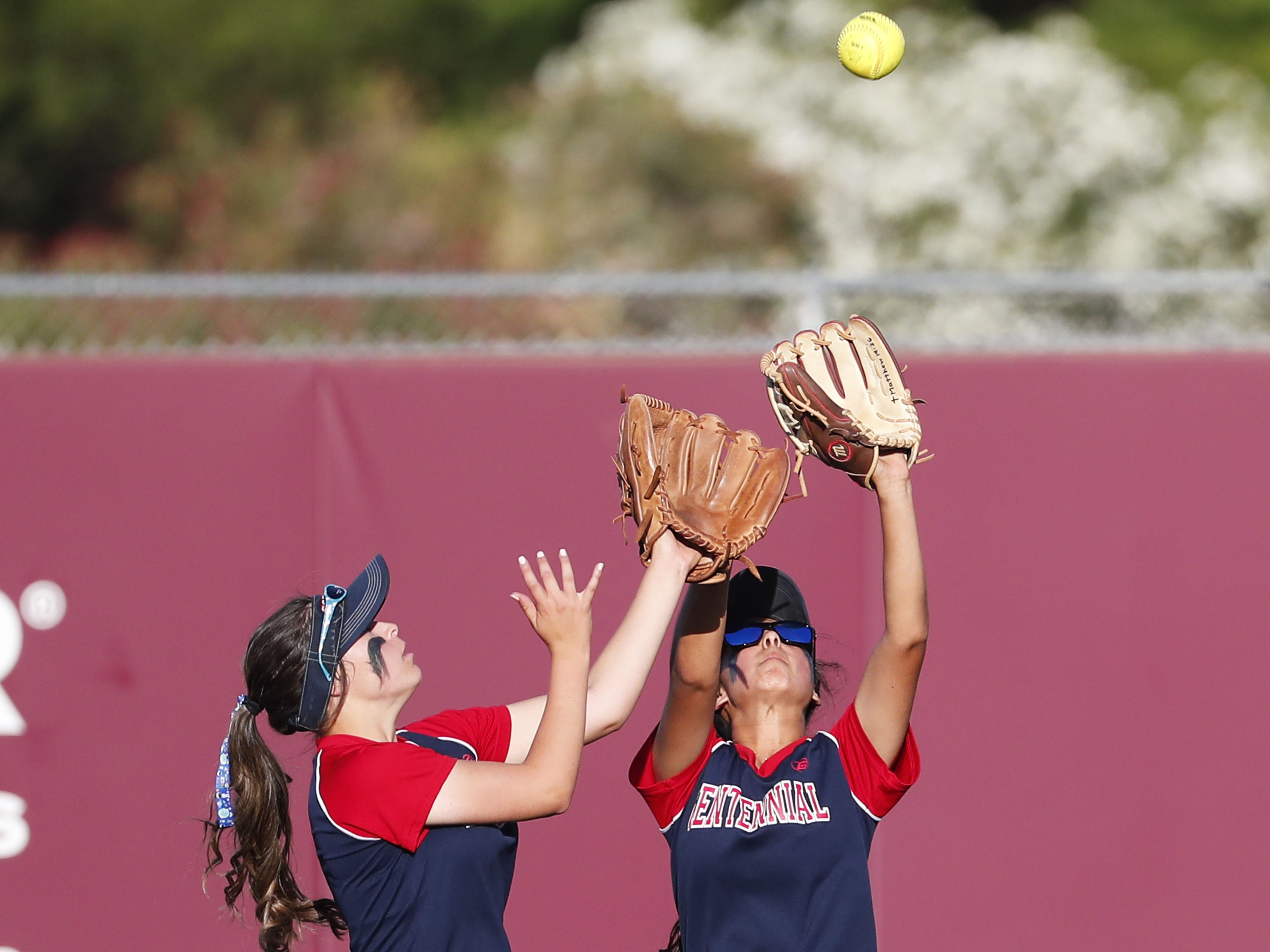Centennial center fielder Jaydin Gonzalez (left) and right fielder Natalie Vasquez collide while catching a ball by Ironwood Ridge during the 5A State Softball Championship in Tempe, Ariz. May 13, 2019.