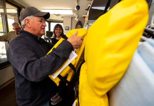Harbormaster Dave Shorkey takes a life jacket off a rack Tuesday, May 14, 2019, at the St. Clair Harbor. Through a partnership with the Sea Tow Foundation, the St. Clair Harbor has received nearly 50 life jackets that can be borrowed.