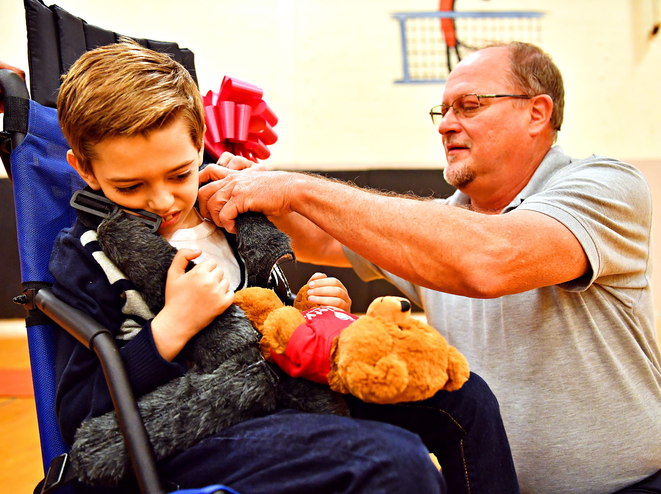 Randy Prunty, of Blackburn's, secures Christian Glass, 9, of Conewago Township in Adams County, into his new adaptable stroller as Prunty partners with Variety, the Children's Charity, based in Pittsburg, to present Blackburn's adaptable equipment to children with disabilities at York Learning Center in North York, Tuesday, May 14, 2019. Dawn J. Sagert photo