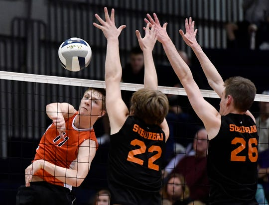 Braden Richard of Central York blasts the ball past York Suburban blockers John Doll (22) and Declan Ridings (26) during the York-Adams League boys' volleyball semifinal game, Monday, May 13, 2019.