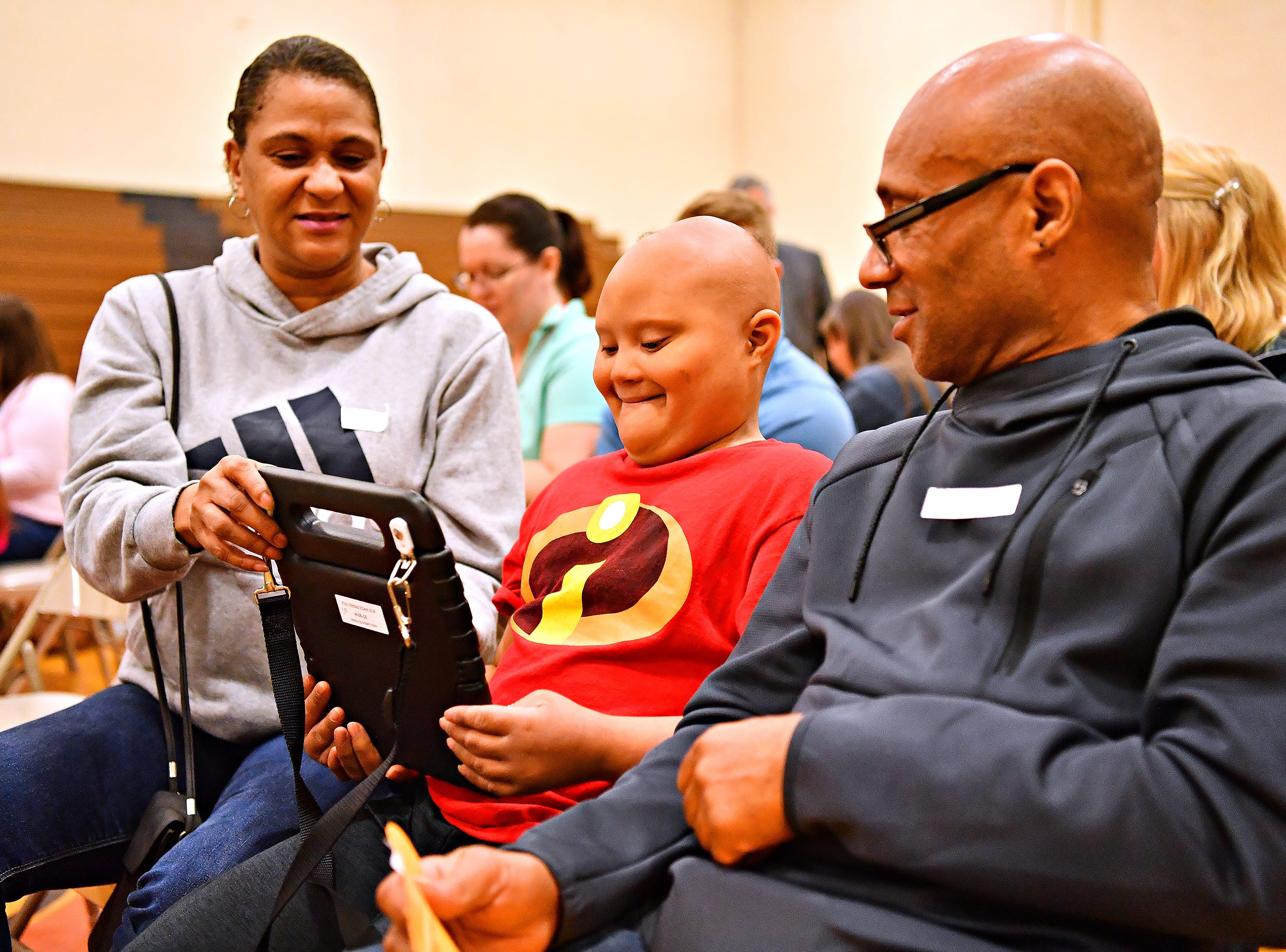 Shontae Stewart, left, and Charles Stewart, right, look on as their son Samuel Stewart, 10, checks out the camera feature on his new communication device from Variety, the Children's Charity, an organization based in Pittsburg that provides adaptable equipment and communication devices to children with disabilities, at York Learning Center in North York, Tuesday, May 14, 2019. Upon receiving the device, Samuel, who was born with Down syndrome, used the device to tell his parents he wanted a dvd and to go home. Dawn J. Sagert photo