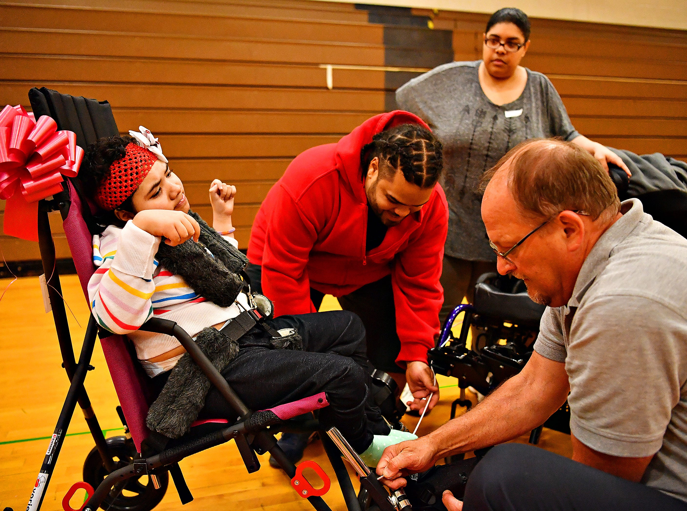 From right in front, Randy Prunty, of Blackburn's, shows Franciso Rivera how to secure his daughter Maydaly's Rivera, 11, in her new adaptable stroller while Maydaly's' mother Melissa Torres looks on as Variety, the Children's Charity, based in Pittsburg, presents adaptable equipment and communication devices to children with disabilities at York Learning Center in North York, Tuesday, May 14, 2019. Dawn J. Sagert photo