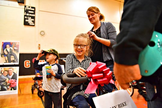 Buffy Eck, right, of Wrightsville, helps her daughter Sophia, 8, secure her hair before putting on her helmet while Sophia's brother Tucker, 5, stands nearby as Variety, the Children's Charity, based in Pittsburg, presents adaptable equipment and communication devices to children with disabilities at York Learning Center in North York, Tuesday, May 14, 2019. Dawn J. Sagert photo