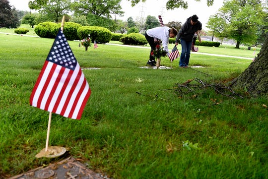 Gold Star mother Deb Etheridge and several volunteers place flags on veteran graves at Prospect Hill Cemetery in preparation for Memorial Day, Monday, May 13, 2019.