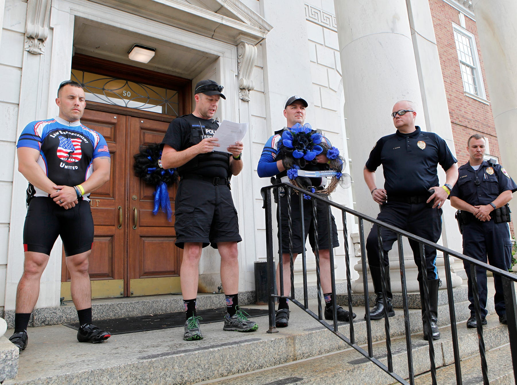 Cory Reader, president of the PA Division of Law Enforcement United, center, reads Officer Alex Sable's information from the Officer Down Memorial Page, during a brief stop at York City Police headquarters, Saturday, May 11, 2019. Officer Mike Watts, left, from Plymouth Township PA, was riding in honor of Officer Sable. 