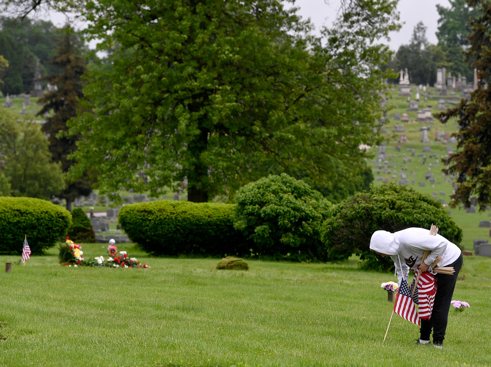 DeVaughn Clauser 15, helps Gold Star mother Deb Etheridge, not shown, place flags on veteran graves at Prospect Hill Cemetery in preparation for Memorial Day, Monday, May 13, 2019. Clauser and two other National Honors Society members from Dover High School assisted in the flag placing.John A. Pavoncello photo