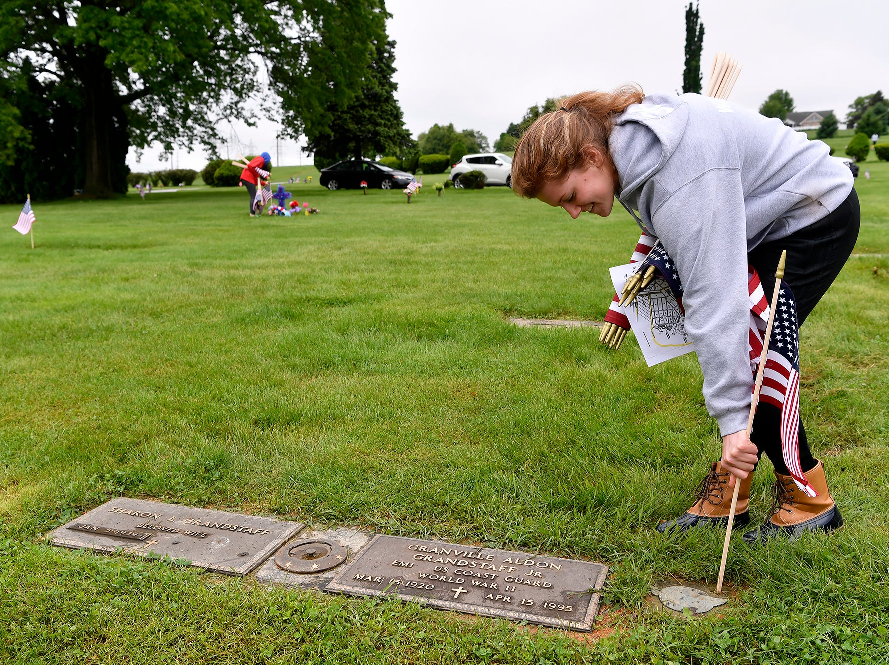Sierra Weaver, 15, helps Gold Star mother Deb Etheridge, not shown, place flags on veteran graves at Prospect Hill Cemetery in preparation for Memorial Day, Monday, May 13, 2019. Weaver and two other National Honors Society members from Dover High School assisted in the flag placing.John A. Pavoncello photo