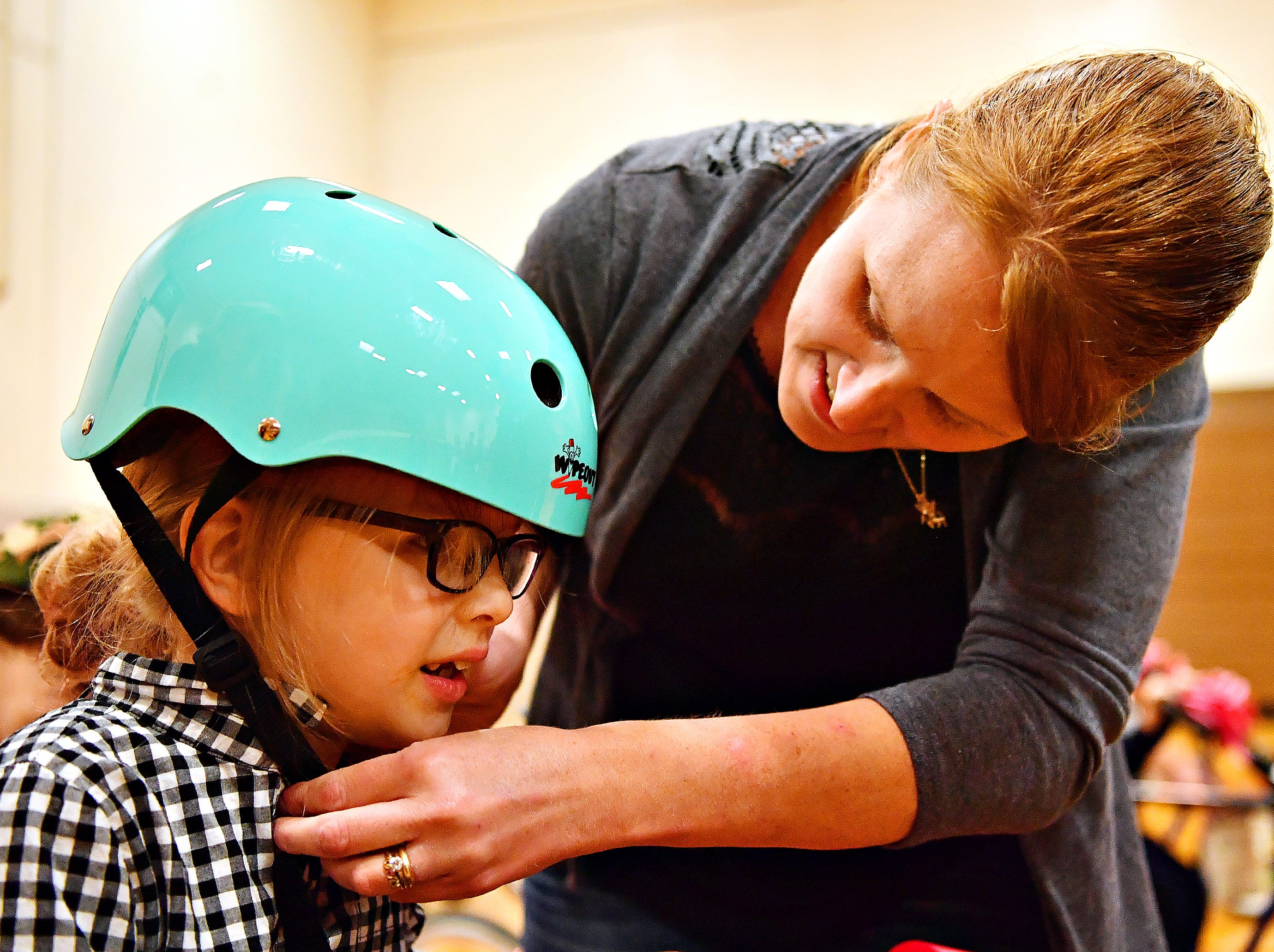 Buffy Eck, right, helps her daughter Sophia Eck, 8, both of Wrightsville, secures Sophia's helmet as Variety, the Children's Charity, based in Pittsburg, presents adaptable equipment and communication devices to children with disabilities at York Learning Center in North York, Tuesday, May 14, 2019. Dawn J. Sagert photo