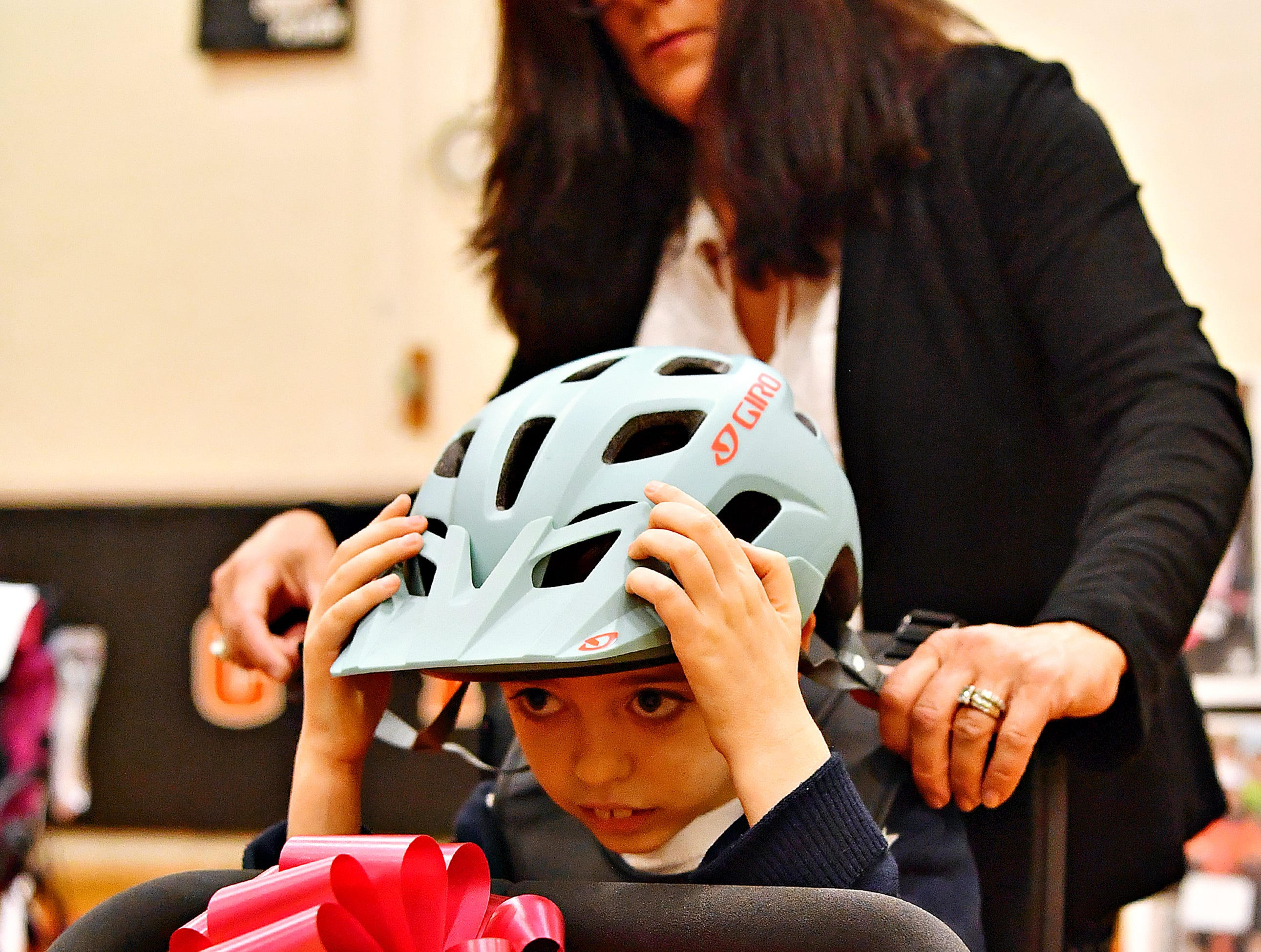 Christian Glass, 9, of Conewago Township in Adams County, secures his helmet as his mother Lisa Glass adjusts his adaptable bicycle as Variety, the Children's Charity, based in Pittsburg, presents adaptable equipment and communication devices to children with disabilities at York Learning Center in North York, Tuesday, May 14, 2019. Dawn J. Sagert photo