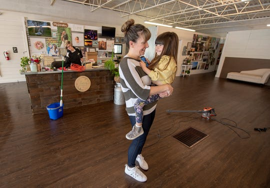 Krista Spillman, left, spends a moment with her 4-year-old daughter Charlee while cleaning her photography studio, Loving Memories Photography & Design, in a former lighting store along North Hills Road in Springettsbury Township. She worries that two upcoming road projects will affect her business after spending $30,000 remodeling.