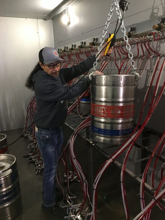 Tom Tanouye, general manager of the Growler Guys in South Reno, lifts a keg into place using a keg crane. The Growler Guys is opening May 15, 2019, with a grand opening celebration May 17-18.