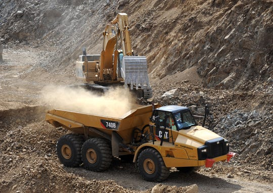 A mineral ore truck is loaded with material in an open pit mine.