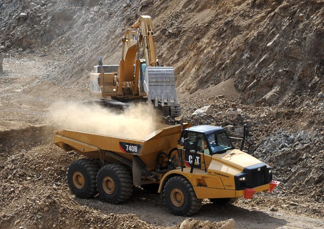 An earth ore truck is loaded with materials at an open-pit mine.