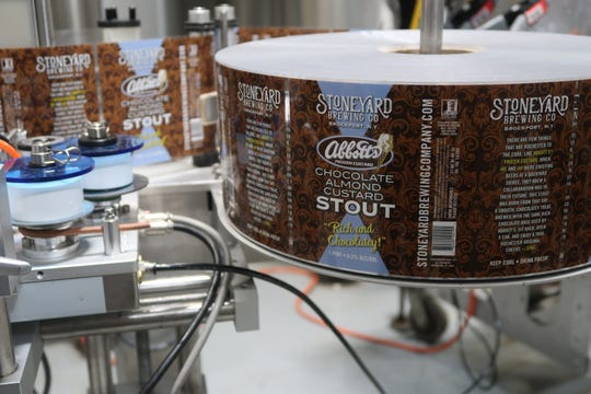 Labels for Stoneyard's Chocolate Almond Custard Stout, a collaboration with Abbott's Frozen Custard, on the mobile canning line Tuesday at the brewery in Brockport.