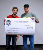 Collin Box of Capital Futbol Club and Siletz Indians charitable fund board member Kurt Arden hold a check for $5,000 awarded to Capital Futbol Club by the Confederated Tribes of Siletz Indians of Oregon.