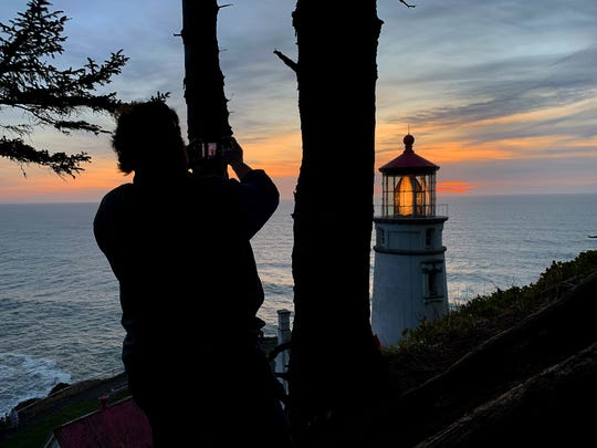A hiker takes a photo of the lighthouse at sunset at Heceta Head.