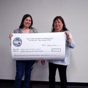 Shelby Maenz of Salem-Keizer Public Schools and Siletz Indians charitable fund board member Cheryl Lane hold a check for $3,100 awarded to the Salem-Keizer Public Schools Indian Education Department by the Confederated Tribes of Siletz Indians of Oregon.
