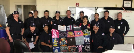 San Angelo Fire Department presents Joyce Lay a handmade t-shirt quilt.
