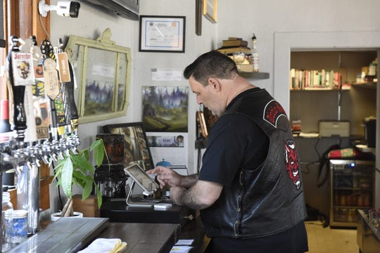 Travis Graham takes an order from a customer at Books n Brewz Pizzeria on Tuesday, May 14.