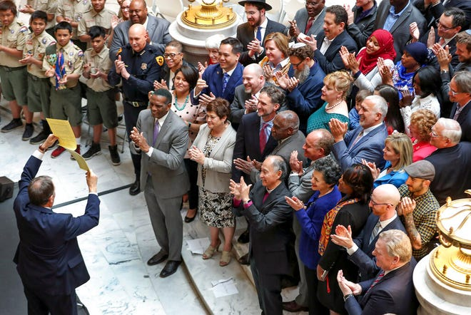 FILE - In this April 2, 2019, file photo, Utah Gov. Gary Herbert holds up S.B. 103, Victim Targeting Penalty Enhancements, after signing it into law in a public ceremony marking the moment Utah's comprehensive bill to prevent hate crimes became law at the Utah State Capitol Rotunda, in Salt Lake City. Lawmakers passed 574 bills this year, setting a record, and most of those new laws will go into effect on Tuesday, May 14, 2019, 60 days after the end of the short legislative session. (Steve Griffin/The Deseret News via AP, File)