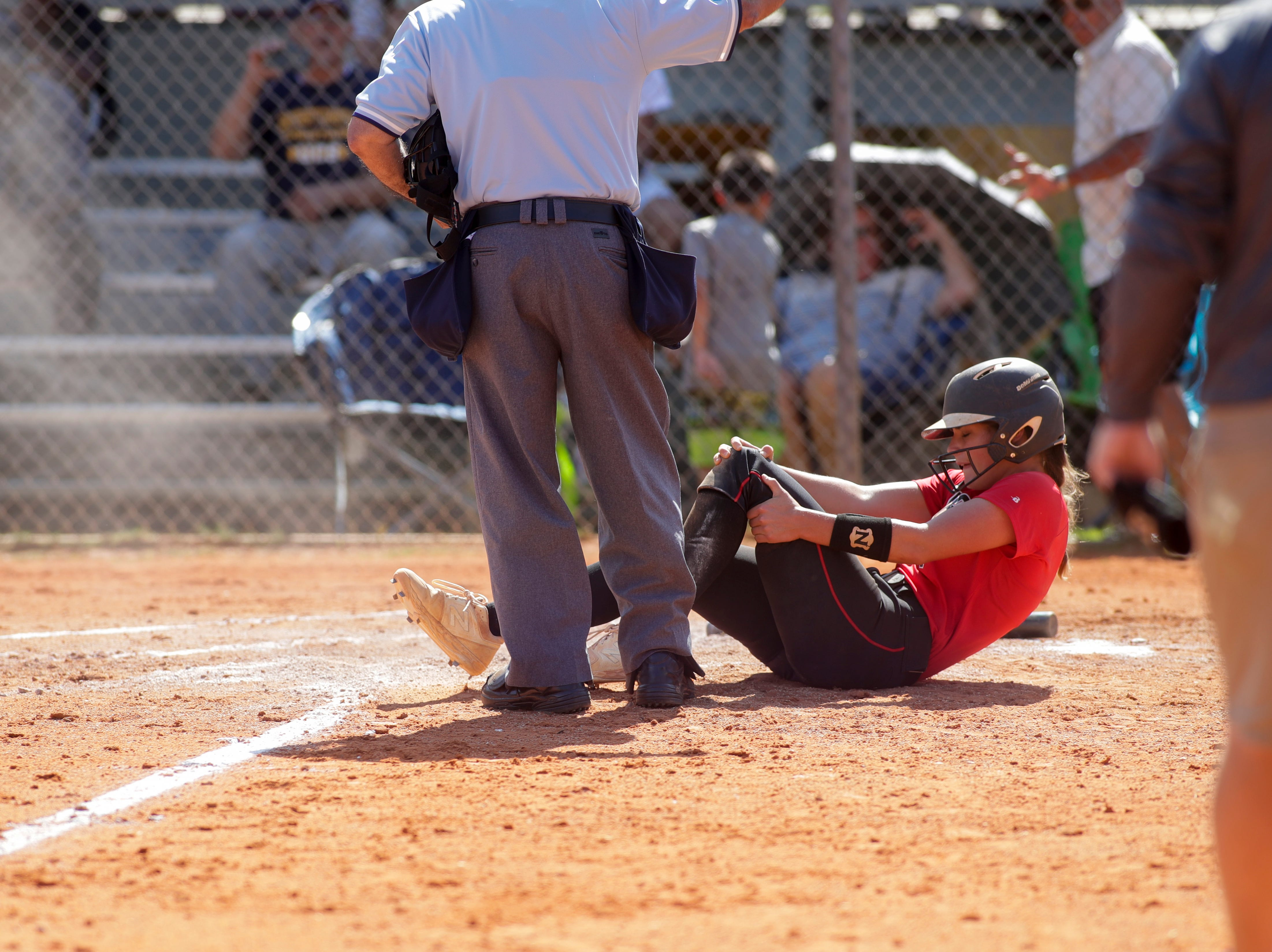 North Florida Christian's Chloe Culp (1) goes down after being knocked over by the catcher as she got to home plate during the 1-3A regional final game between NFC and University Christian at NFC Tuesday, May 14, 2019. UC defeated NFC 16 to 11 to advance to the state tournament.