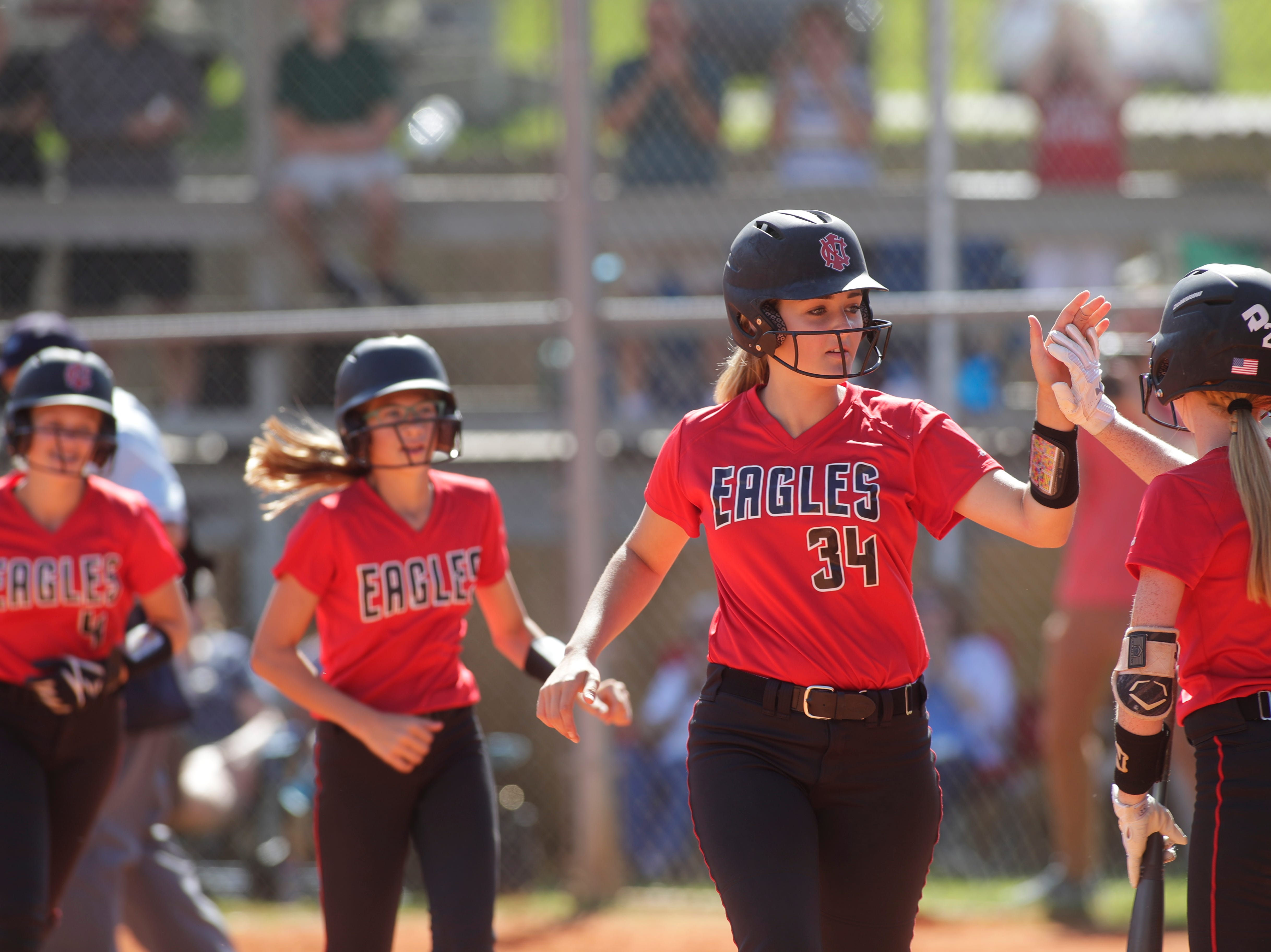 North Florida Christian's Ramsey Shiver (34) high fives a teammate after scoring a run during the 1-3A regional final game between NFC and University Christian at NFC Tuesday, May 14, 2019. UC defeated NFC 16 to 11 to advance to the state tournament.