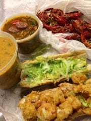 Takeout dishes, including crawfish étouffée, gumbo, the boiled crawfish and a shrimp po' boy from New Orleans Seafood.